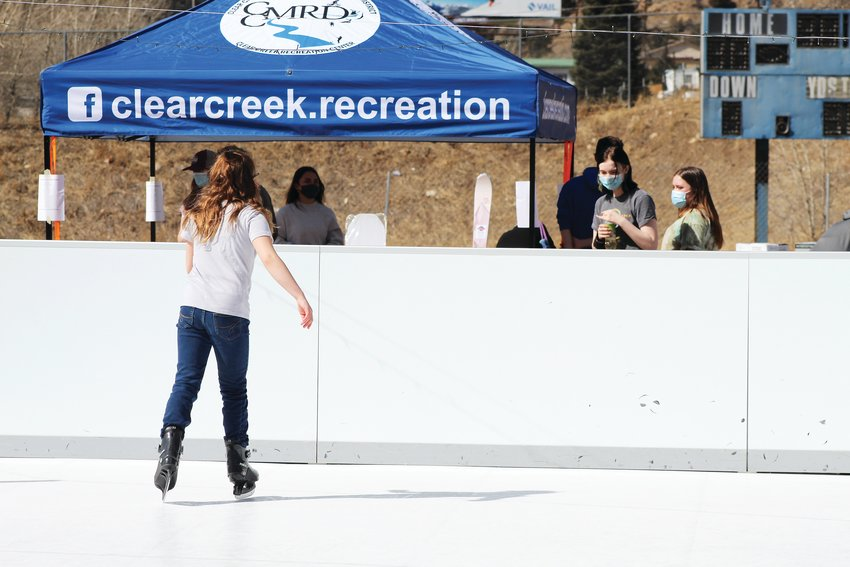 Audrey Amann, 10, skates as people survey the silent auctions under the nearby tent at Saturday's skating and bingo fundraiser for Clear Creek High School.