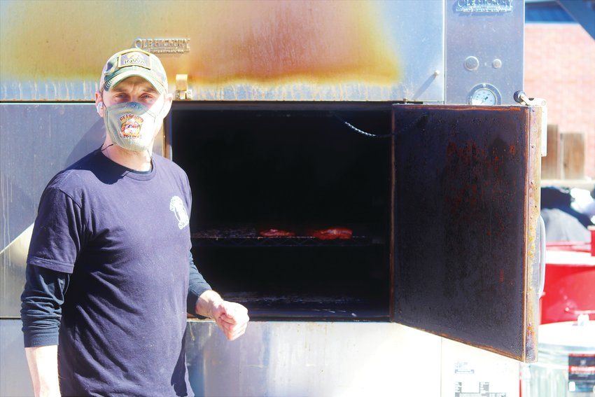 Jacob Viers stands in front of his barbecue smoker at Seasoned Swine.