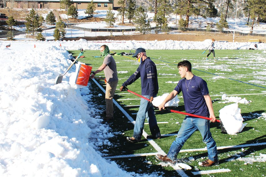 From left, counselor Brian Tracey, principal Chris Gould and freshman linebacker Mateo Gonzalez clear snow off Clear Creek High School's new football field Thursday. Hundreds of students, parents, staff and community members helped clear snow Wednesday through Saturday morning to get the field cleared in time for kick-off Saturday afternoon.