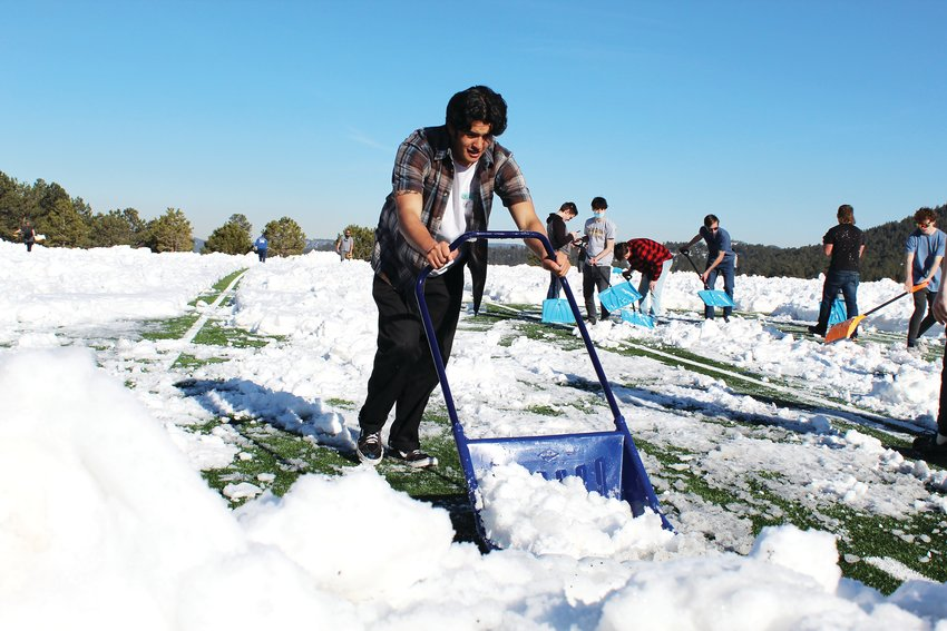 Senior tight end/defensive end Armando Acosta clears snow off Clear Creek High School's new football field Thursday. Hundreds of students, parents, staff and community members helped clear snow Wednesday through Saturday morning to get the field cleared in time for kick-off Saturday afternoon.