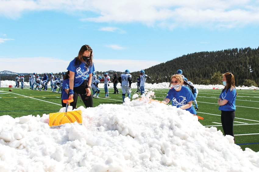 Clear Creek football's student managers clear snow off the sidelines shortly before Saturday's game at Golddigger Stadium.