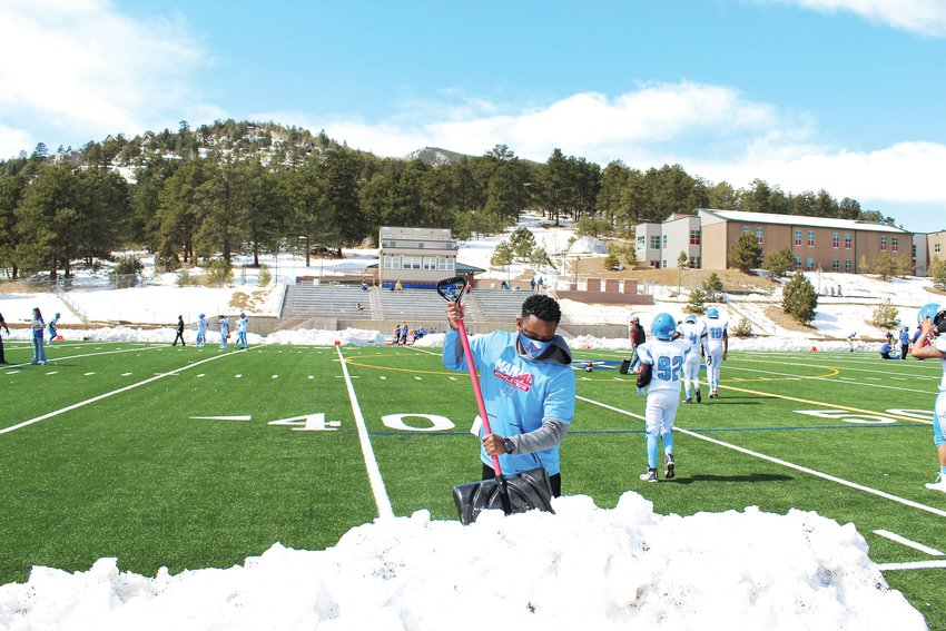 Doug Clinkscales, Manual High School's athletic director, shovels snow off the sidelines to make room for the officials and chain crew shortly before Saturday's game at Golddigger Stadium.