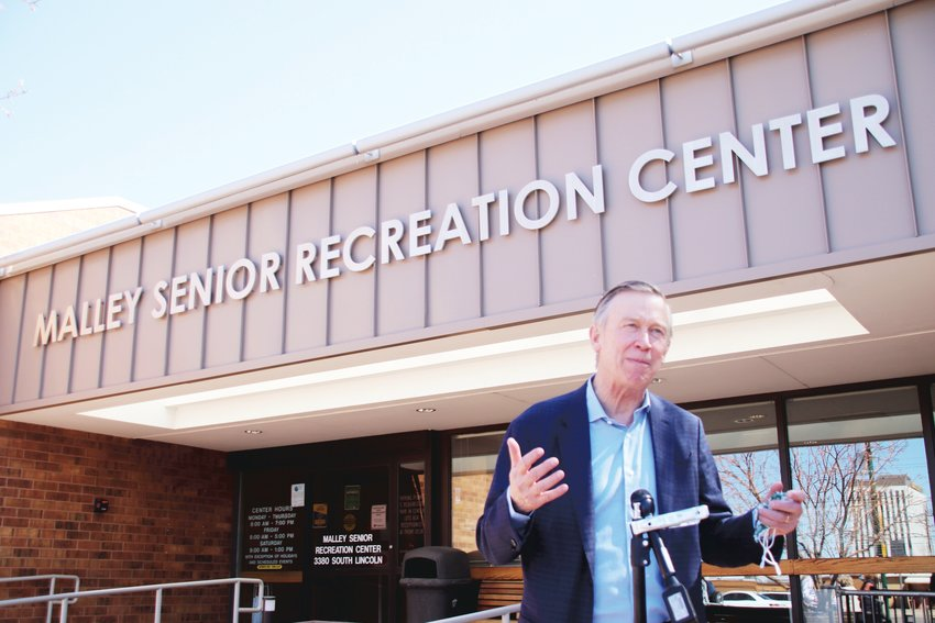 U.S. Sen. John Hickenlooper speaks outside the Malley Senior Recreation Center in Englewood on April 1. Hickenlooper praised the impact federal funds have had on clinics like the one held inside Malley, which is focusing on people who have difficulty accessing larger or more distant vaccination sites.