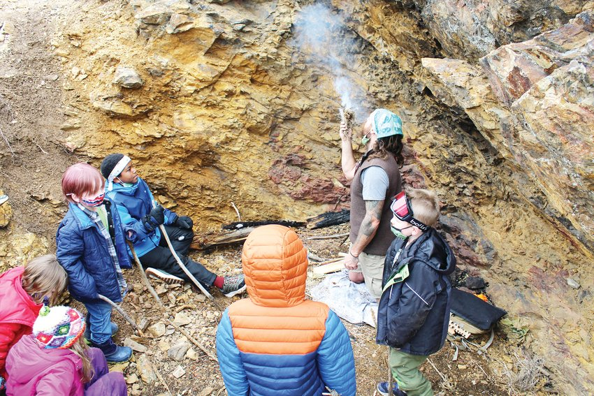 Roary Archibald, a wilderness educator, demonstrates how to start a fire for the Kidz Korner spring break program Thursday on the Prospector Trail above Building 103.
