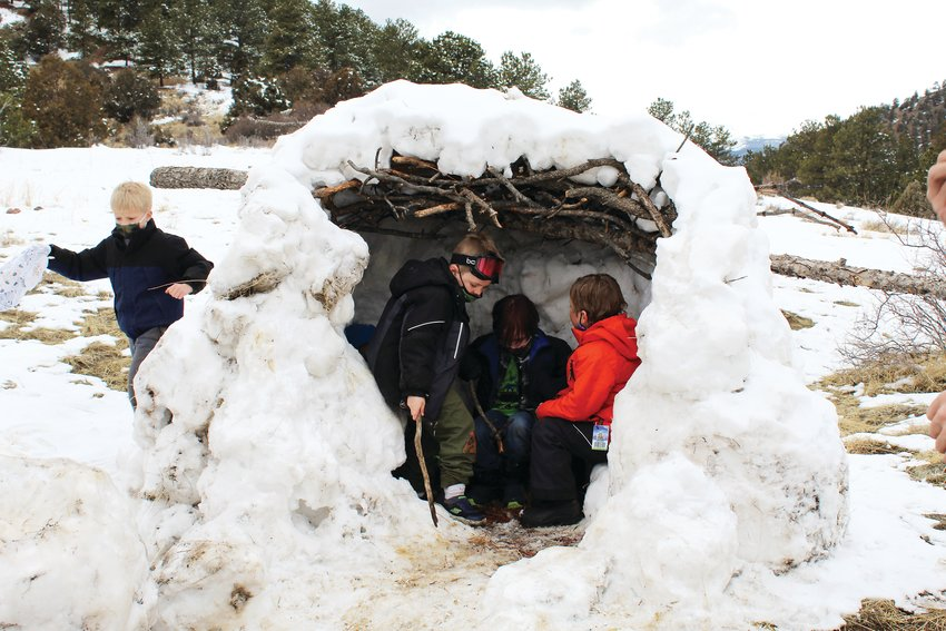 On Thursday, Kidz Korner participants enjoy a shelter they built along the Prospector Trail above Building 103. As part of their spring break program, the children build the shelter over the previous three days, creating it out of compressed snow and lattice-worked sticks.