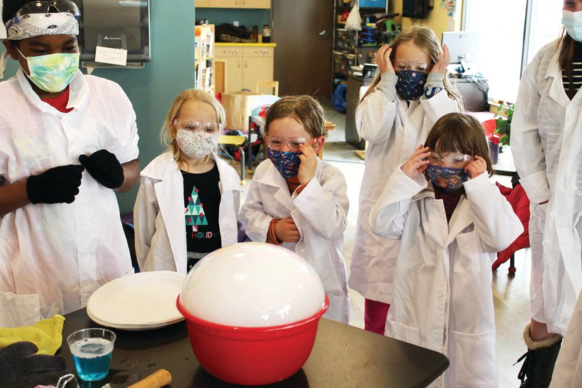 Kidz Korner participants watch with excitement as a large bubble begins to form over the dry ice during their spring break program Thursday.