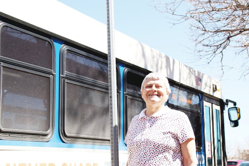 Andrea Suhaka, the leader of a new nonprofit that works to broaden access to transportation for people who can't or don't drive, stands at a bus stop on Arapahoe Road near Interstate 25 as a bus rolls past behind her.