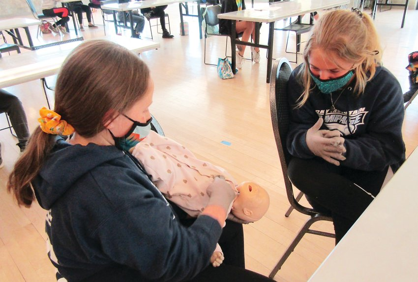 Fifth grader Clare Sweet practices techniques to stop an infant from choking while Layne Steadman-Lieb watches.