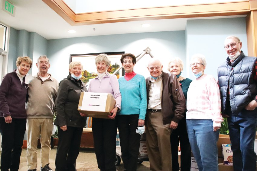Residents of Holly Creek Retirement Community pose together April 15 at the end of a food drive they held to collect items for South Fellowship Food Bank. Vee Henderson, holding a box for the food drive in the middle, organized the drive.