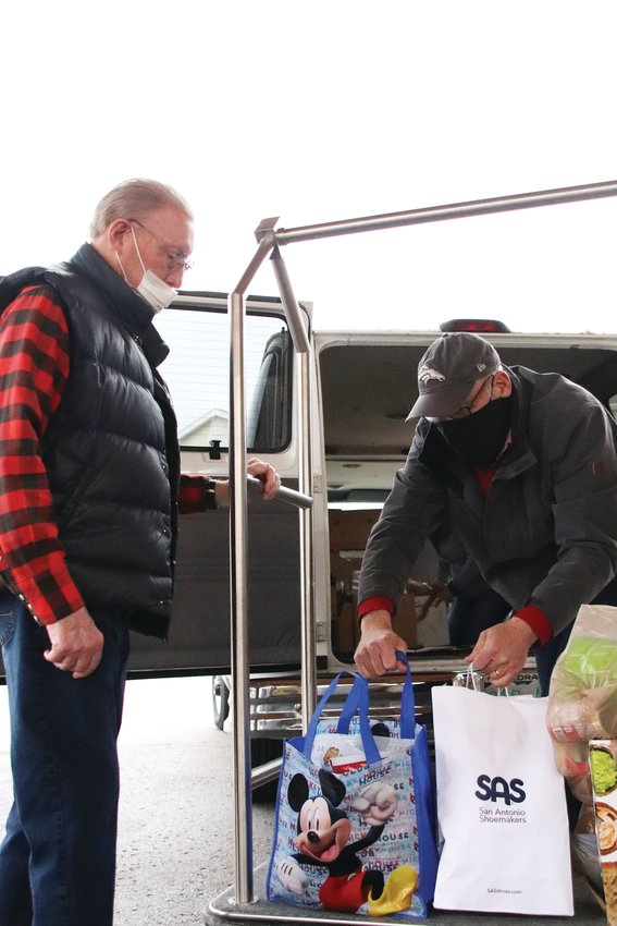 Don Folsom, 80, left, helps pastor Dan Elliott load items from Holly Creek Retirement Community's food drive into a van for South Fellowship Food Bank. South Fellowship Church sits at 6560 S. Broadway near the Littleton-Centennial border.