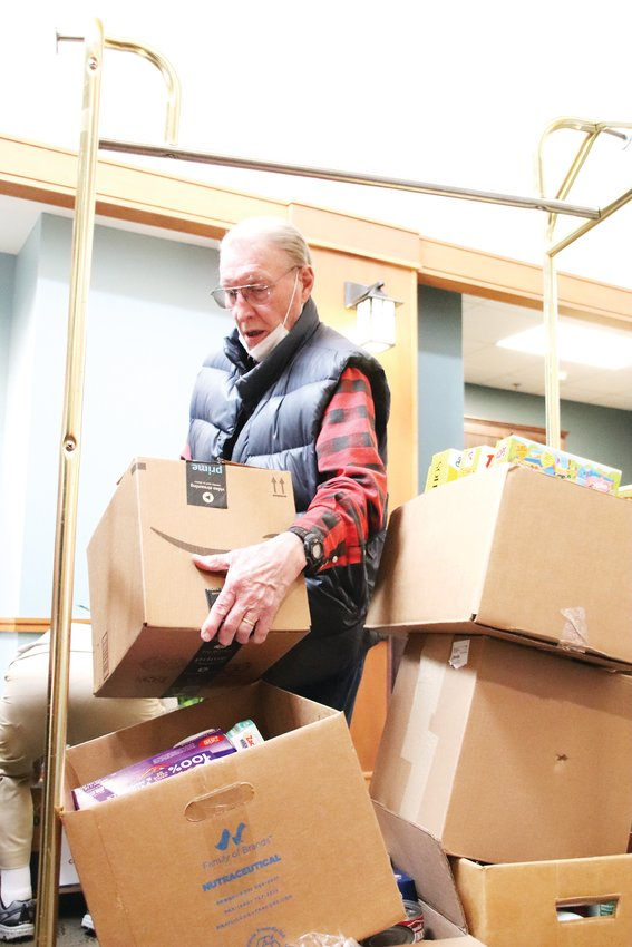 Don Folsom, an 80-year-old resident of Holly Creek Retirement Community, helps load boxes in the Holly Creek lobby at the end of a food drive put on by residents.