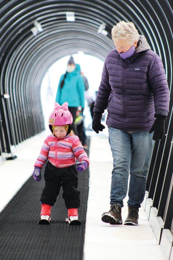 Cameron, 2, and Rae Peters, both of Evergreen, ride the conveyer to the top of Echo Mountain Resort's beginner area Sunday morning.