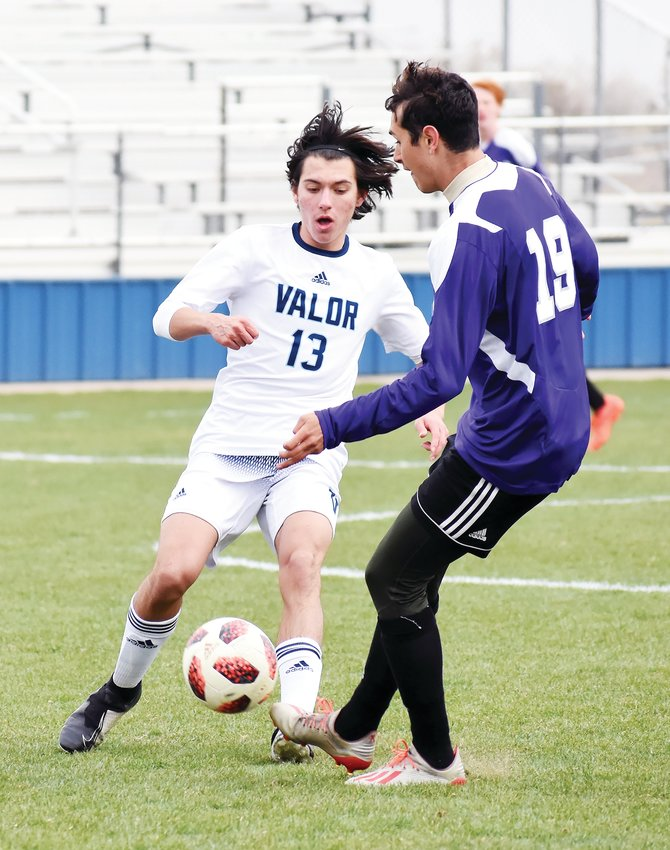 Valor Christian sophomore Duncan Voeglie (13) and Arvada West senior Gabe Schultz (19) battle for possession Monday, April 12, during the Class 5A Jeffco League game at the North Area Athletic Complex.