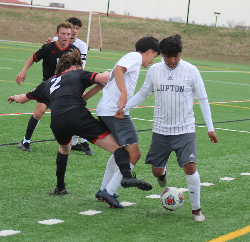 Fort Lupton's Luis Zavala tries to get away from the traffic jam in the first half of his team's state 3A soccer playoff game at Colorado Academy. Zavala's teammate, Jovanny Sixtos gets tangled up with CA's Aaron Rice (2) .