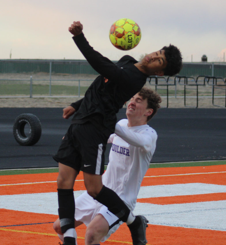 Adams City's Andy Galvan gets to the ball ahead of the onrushing MIcah Garry of Boulder during the first round of the state 5A soccer playoffs April 22.