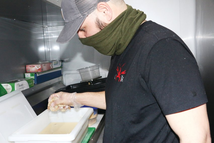 Christian Vice of Cajun King food truck in Castle Rock gets shrimp ready for the popular po' boy sandwich.