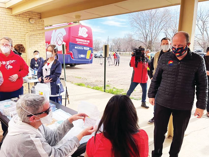 Gov. Jared Polis, right, visits a mobile vaccine clinic, an effort supported by state officials to bring vaccinations sites to locations around Colorado.