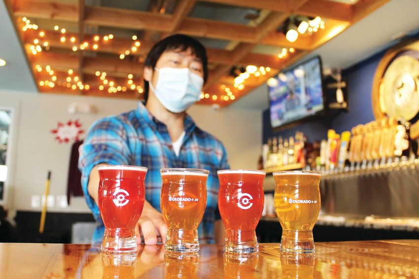 Left: Luke Furey, operations manager at Golden's Colorado + 49 Cidery & Pub, assembles a flight of ciders. The drink, typically made from fermented apples, features a range of dryness to sweetness as well as a variety of flavors. Furey said one of the cidery's most popular ones is a Nordic dry blueberry lavender cider.