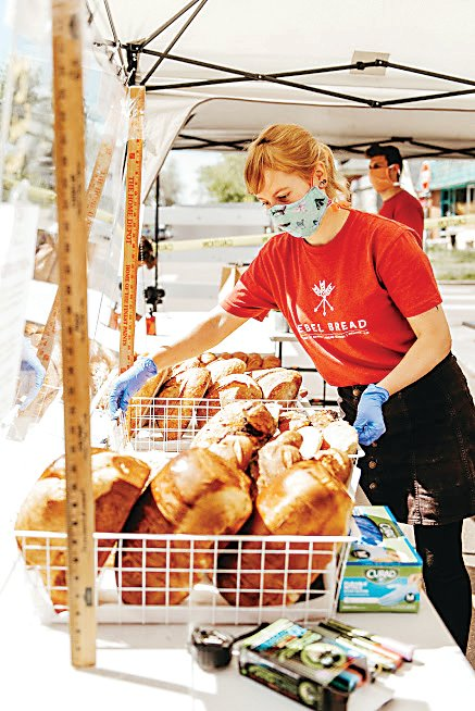 Maya Dank, market director for Rebel Bread, sets the local bakery's items out for sale during last year's South Pearl Street Farmers Market. Rebel Bread is looking forward to being a vendor at both the South Pearl Street Farmers Market and the City Park Farmers Market this year.