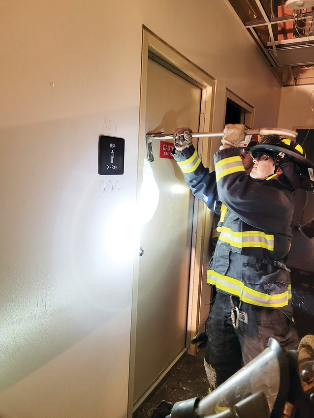 A firefighter uses a tool to break through a door.