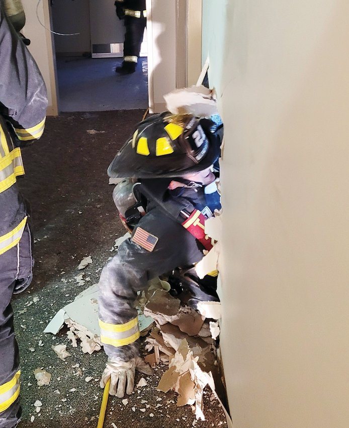 A Golden firefighter breaks through a wall inside the Coors office building at 311 10th Street, which will be torn down in May.
