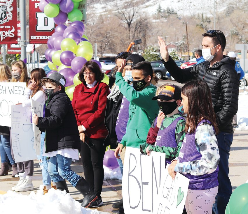 Ben Bontrager, in green, waves to the parading cars along with several of his Fairmount Elementary school friends and supporters from Golden High School.