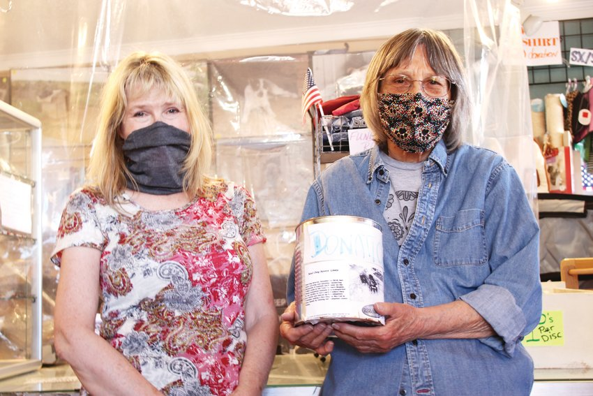 Janet Yench, right, a volunteer for Soul Dog thrift shop in Englewood, holds the shop's donations jar next to Kimberleigh Anders of the Littleton area. The two were running the Soul Dog store on April 30, a few days after a burglary there caused damage that the shop is seeking help to recover from.