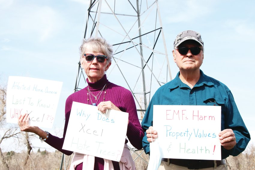 "Leslie Hanks, 70, and John Hanks, 72, stand at the deKoevend Tot Lot park in west Centennial on April 24, holding signs that say ""Affected home owners last to know,"" ""Why does Xcel hate trees?"" and that electromagnetic fields ""harm property values and health."" The Hankses came to the meeting at the park held by Xcel Energy to discuss a plan to upgrade power lines that run through parts of Centennial, Greenwood Village, Littleton, Englewood, Sheridan and Denver."