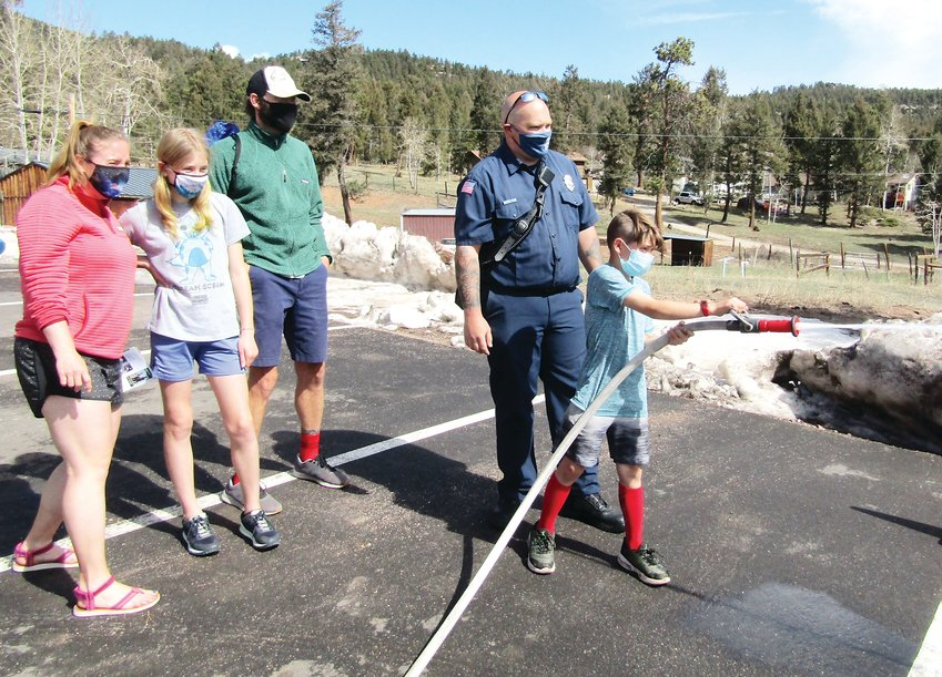 Cooper Susak, 9, tries his hand at operating a wildland fire hose with the help of Elk Creek volunteer firefighter Colt Thiel as his family, mom Tina, sister Amelia, 11, and dad Mark watch.
