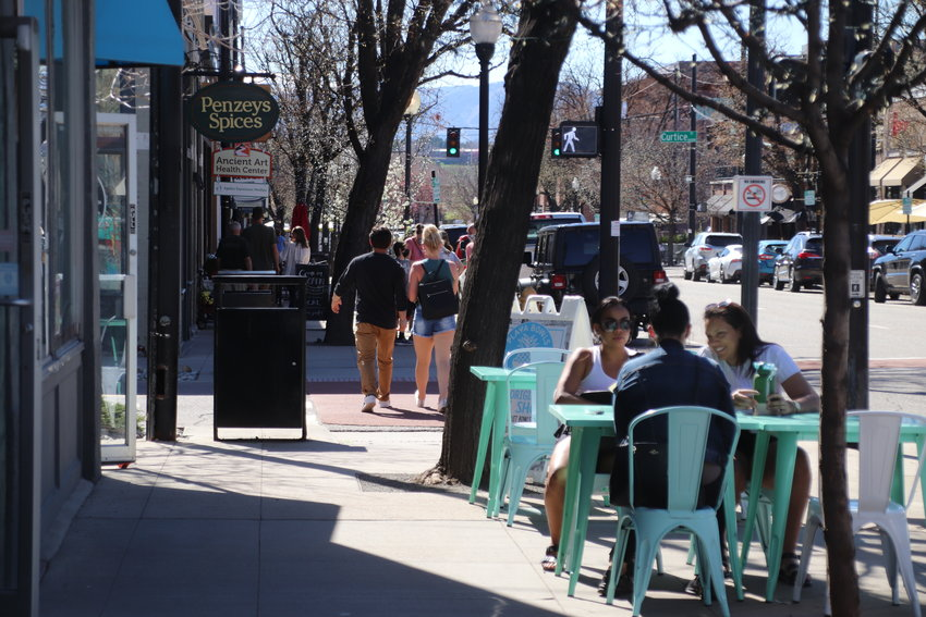 People stroll along Main Street in Downtown Littleton on April 30. City officials and business leaders want to explore the area's future, possibly including narrowing the traffic thoroughfare.