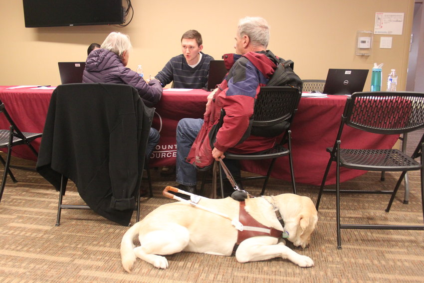 Maryalinda Abernathy, left, and Leonard Decker, right, sit down to discuss housing options with Arapahoe County housing specialist Ben Nichols. Decker's seeing-eye dog Rhett waits on the floor. Windermere residents have an uphill battle to find new housing, Nichols said.