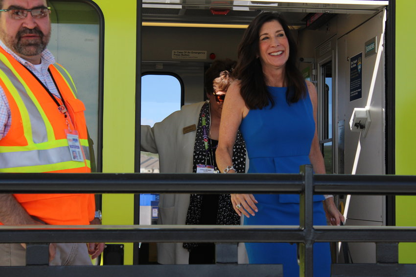 Mayor Jackie Millet steps off the train at the Sky Ridge Station May during the opening day celebration for the Southeast Rail Extension. The Sky Ridge Station is one of three stations part of the project that extends light rail 2.3 miles south.