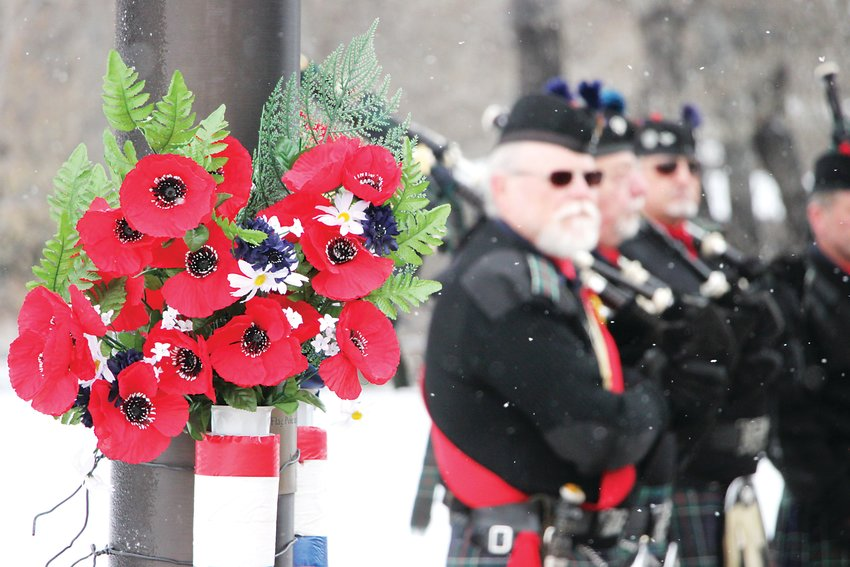 Red poppies, a traditional symbol to remember veterans dating to World War I, hang from the flagpole at the Littleton World War II Memorial.