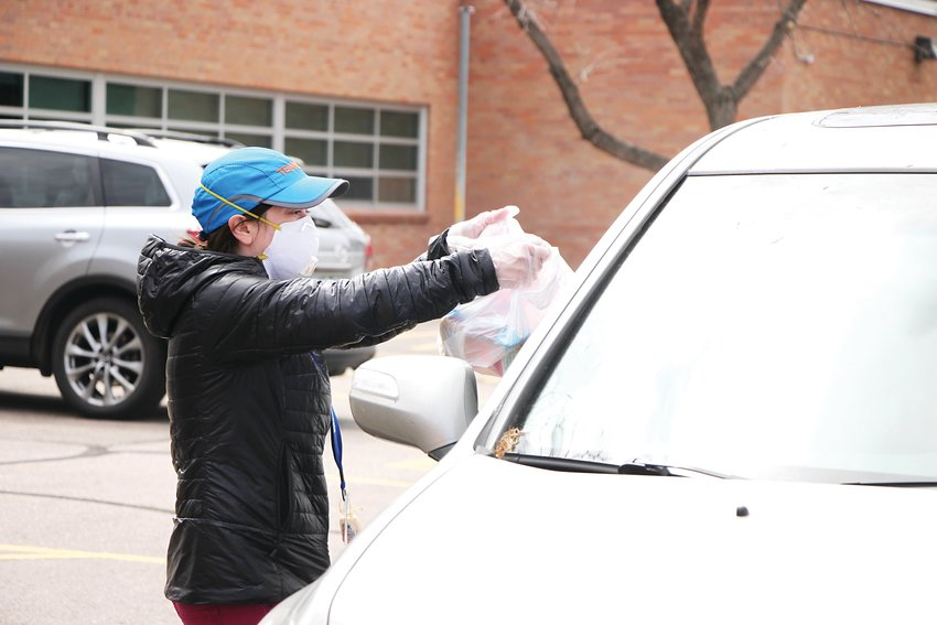 Sarah Kinney passes out meals at East Elementary School in Littleton on March 23. With schools closed because of COVID-19, Littleton Public Schools plans to keep distributing free breakfasts and lunches to all kids under 18 for the foreseeable future.