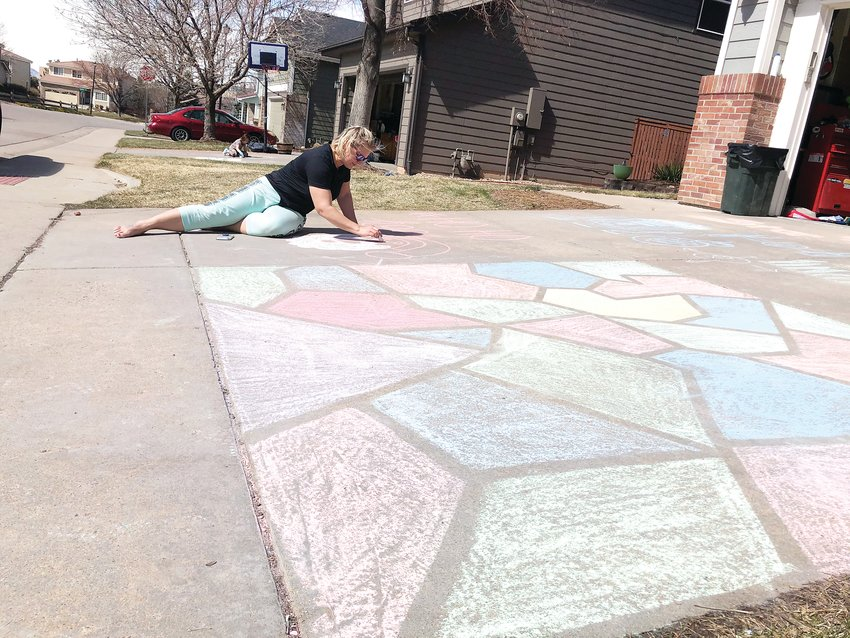 Mandy Henry, 40, works on a chalk drawing of Santa Claus on the driveway of her Highlands Ranch home. Henry's 17-year-old daughter completed the stain-glass style chalk art in the front using painters tape.