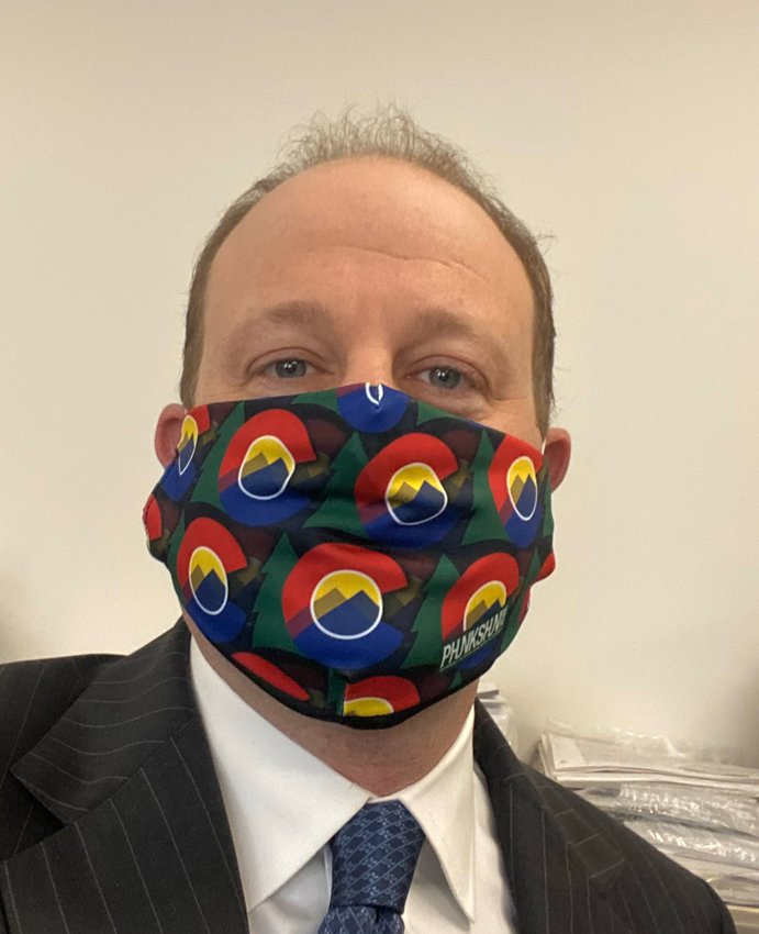 Gov. Jared Polis wears a Colorado-themed mask. The governor on April 3 announced guidance that Coloradans should wear cloth masks or scarves when they leave home for essential activities such as grocery shopping. But medical masks should be reserved for workers who need them, Polis said.