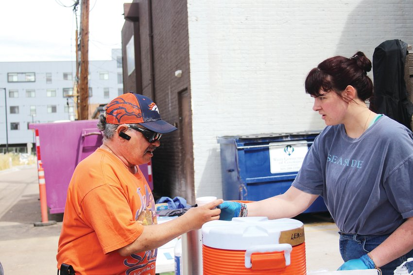 Larry Anderson receives a cup of coffee from Makayla Creech, a volunteer for Movement 5280, a group that assists at-risk and homeless young adults and other homeless residents. The organization is part of Change the Trend's effort to deliver groceries to vulnerable populations in Englewood, Littleton and Sheridan.