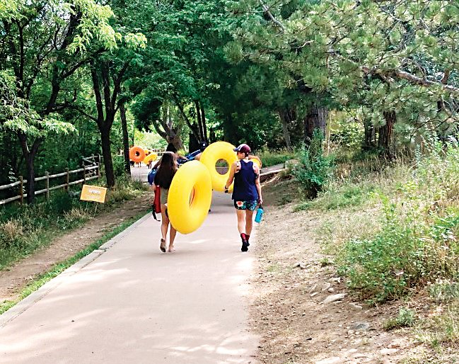 Tubers walking along Clear Creek in Golden on Aug. 4.