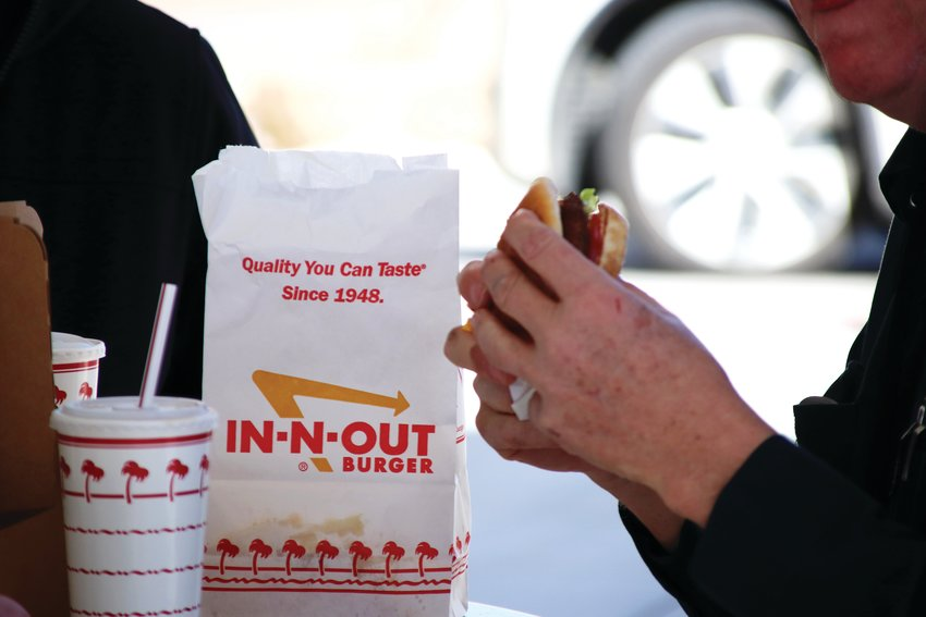 Employees at the new In-N-Out in Lone Tree grab burgers during the restaurant's Feb. 22 grand opening.