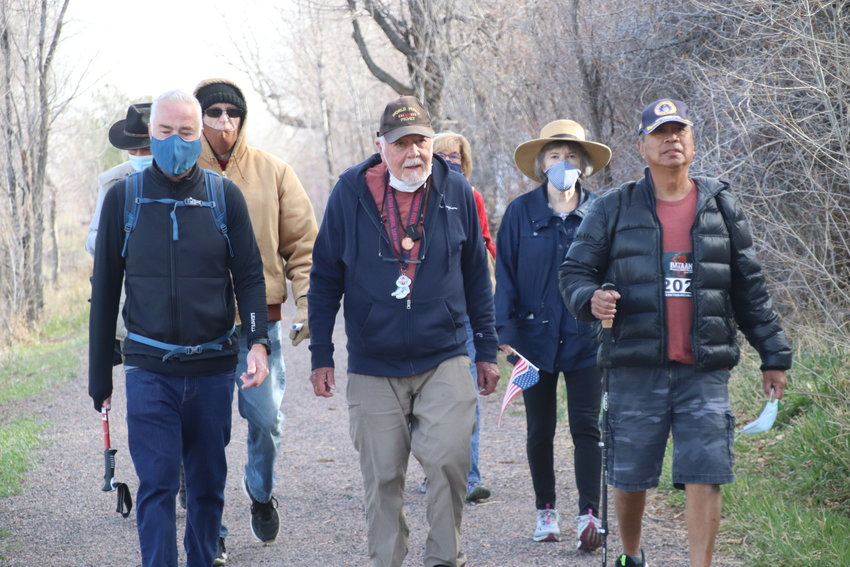 Frank Francone, center, marches with son Stuart Francone, left, Air Force veteran Mike Simbre, right, and several friends in Littleton on April 9. An army veteran, Francone set out to commemorate the Bataan Death March of 1942.