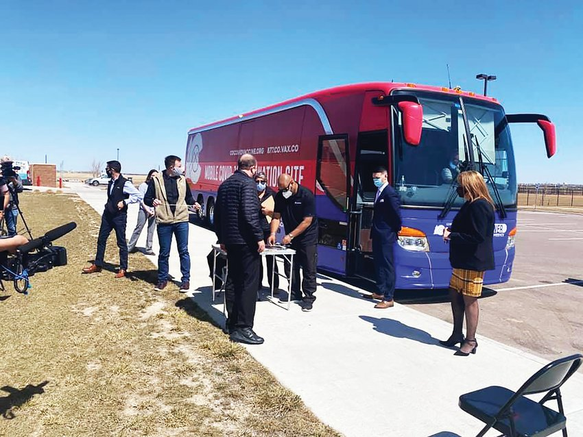 Gov. Jared Polis, center, visits a mobile vaccine clinic, an effort supported by state officials to bring vaccinations sites to locations around Colorado. The state has two bus routes and was to announce a third soon.