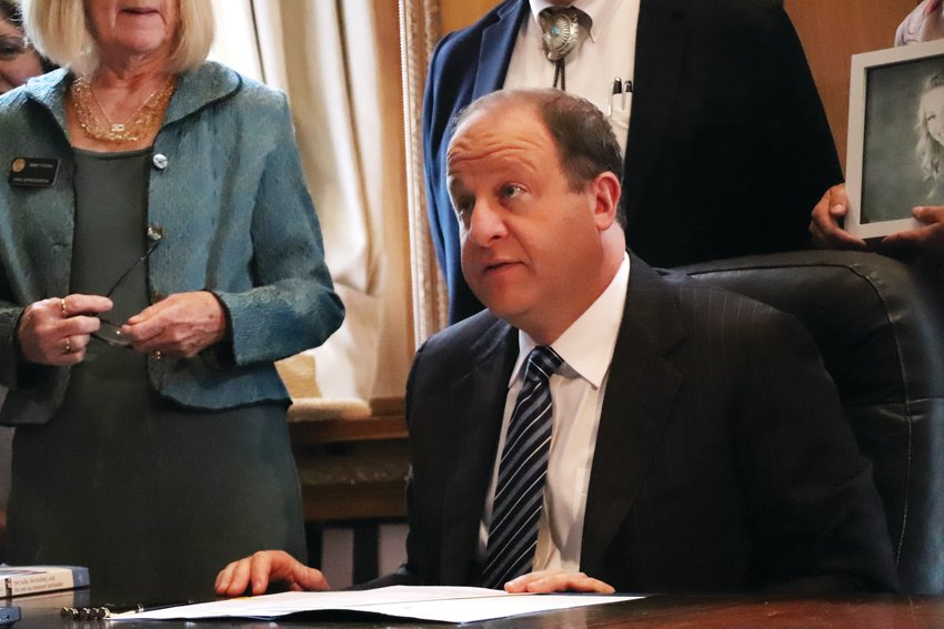 Gov. Jared Polis sits at his desk June 7 in the state Capitol to sign a bill aimed at addressing bullying policy among school districts in the state.