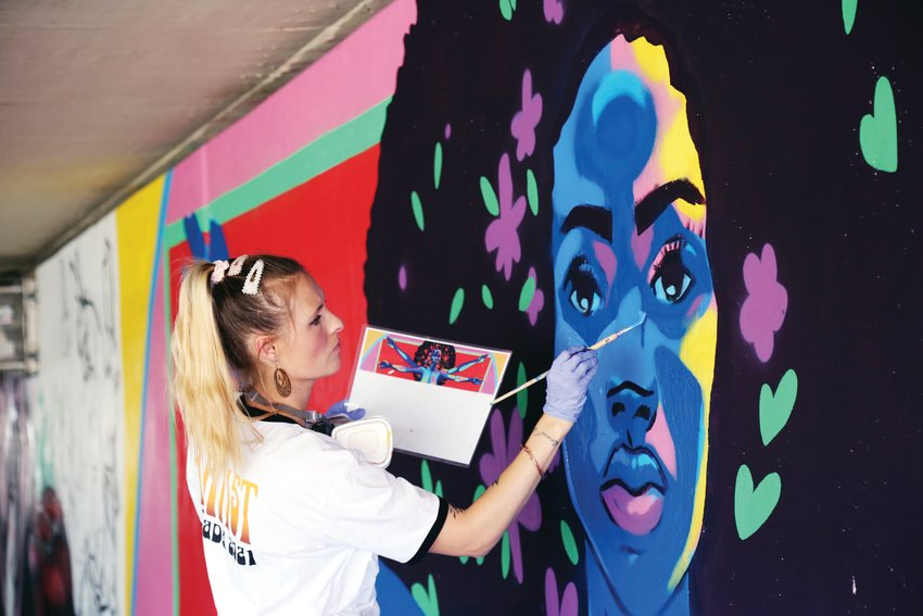 Coco Jenkins paints a mural in an underpass along the Ralston Creek Trail.