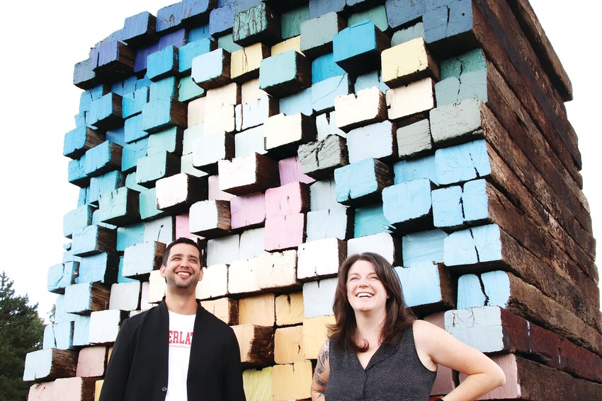 """Marcus Turner, the director of communications and audience services at the Arvada Center for the Arts and Humanities, left, and Emily Grace King, exhibition manager for the Arvada Center, stand Sept. 16 near a sculpture at the center's """"sculpture field."""" The piece by Scottie Burgess, made with railroad ties and wood paint, is titled """"Ties Forward."""""""