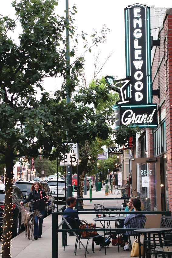 In a file photo, a small group sits outside the Englewood Grand bar Oct. 1 as a pedestrian walks with a dog on downtown Englewood's downtown South Broadway corridor.