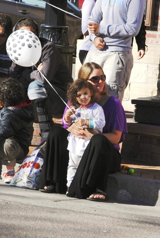 Tamara Goff sits with her daughter, Kaiya Bishop, 2, who watched the parade as it turned down 13th street from Washington Ave.