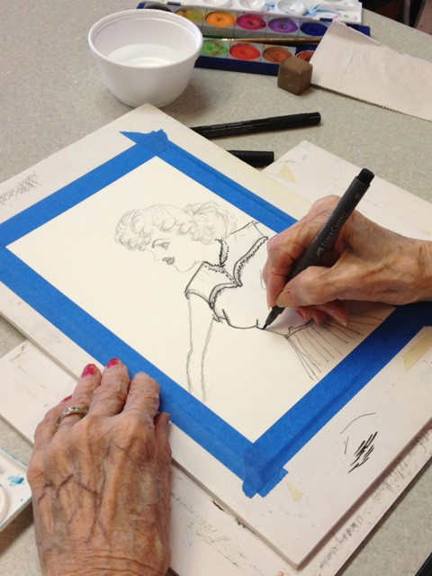 Sue Rhodes creates an image of a woman during a painting class at Emeritus Denver.