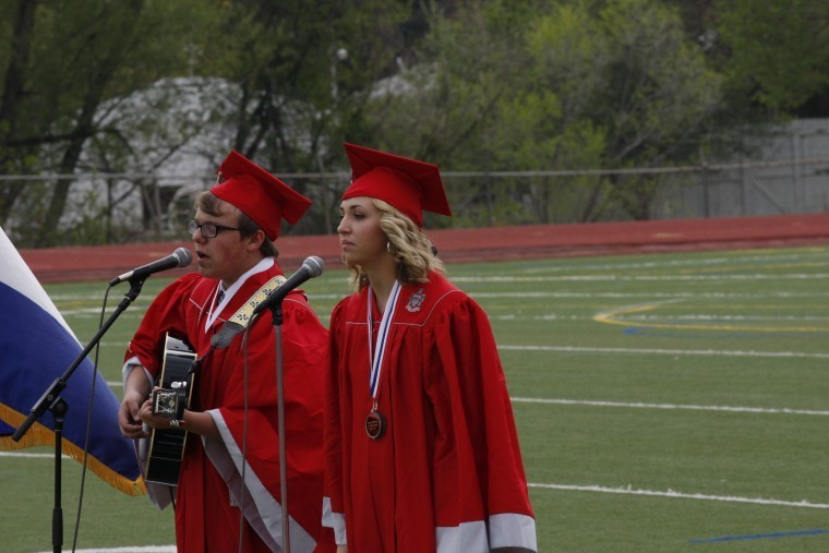 "Devon Hilderbrandt plays the guitar and blends his voice with Tess Robinson on the song, ""Against the Grain"" during Heritage High School's May 18 commencement ceremony. Photo by Tom Munds"