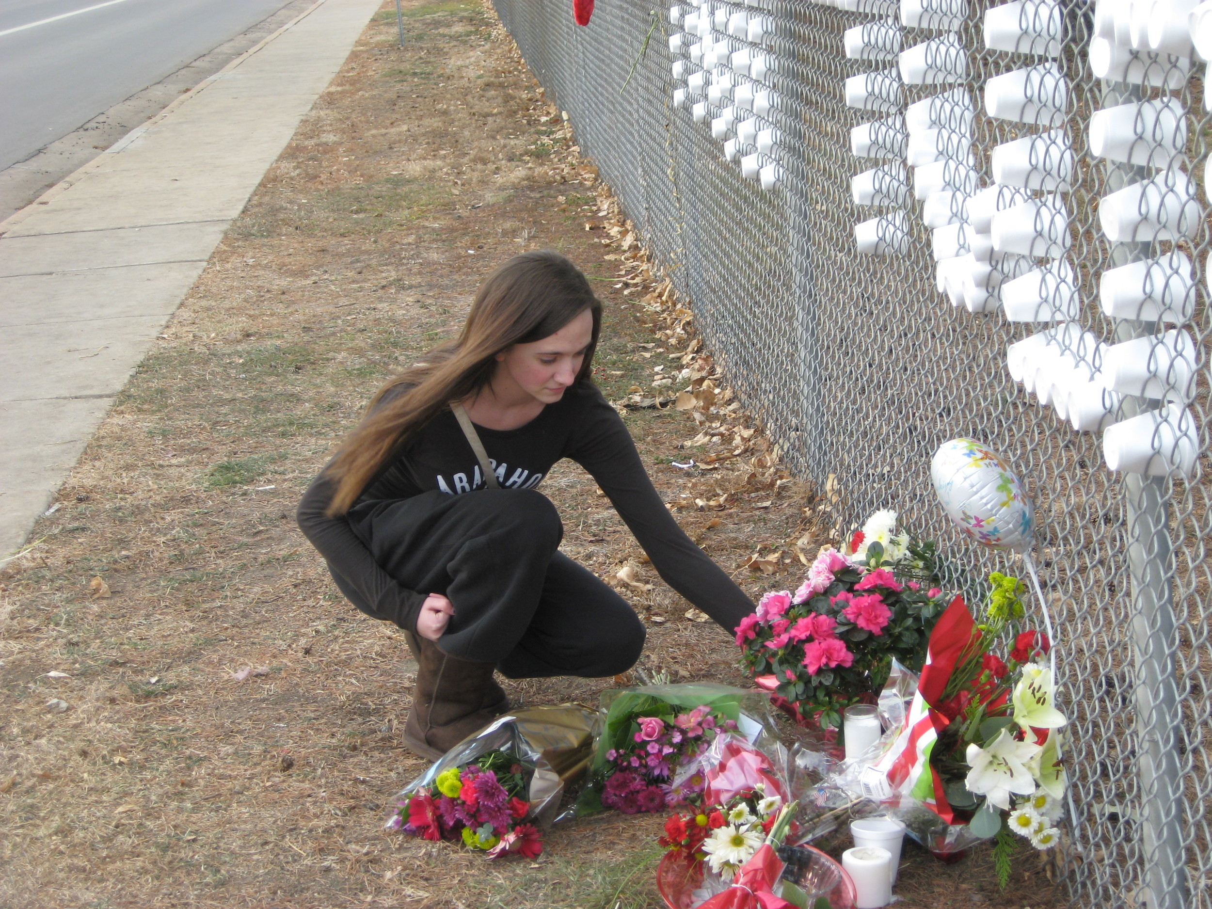 Kaylee Eastridge, an Arapahoe High junior, looks over the flowers left behind as a show of support for Claire Davis.
