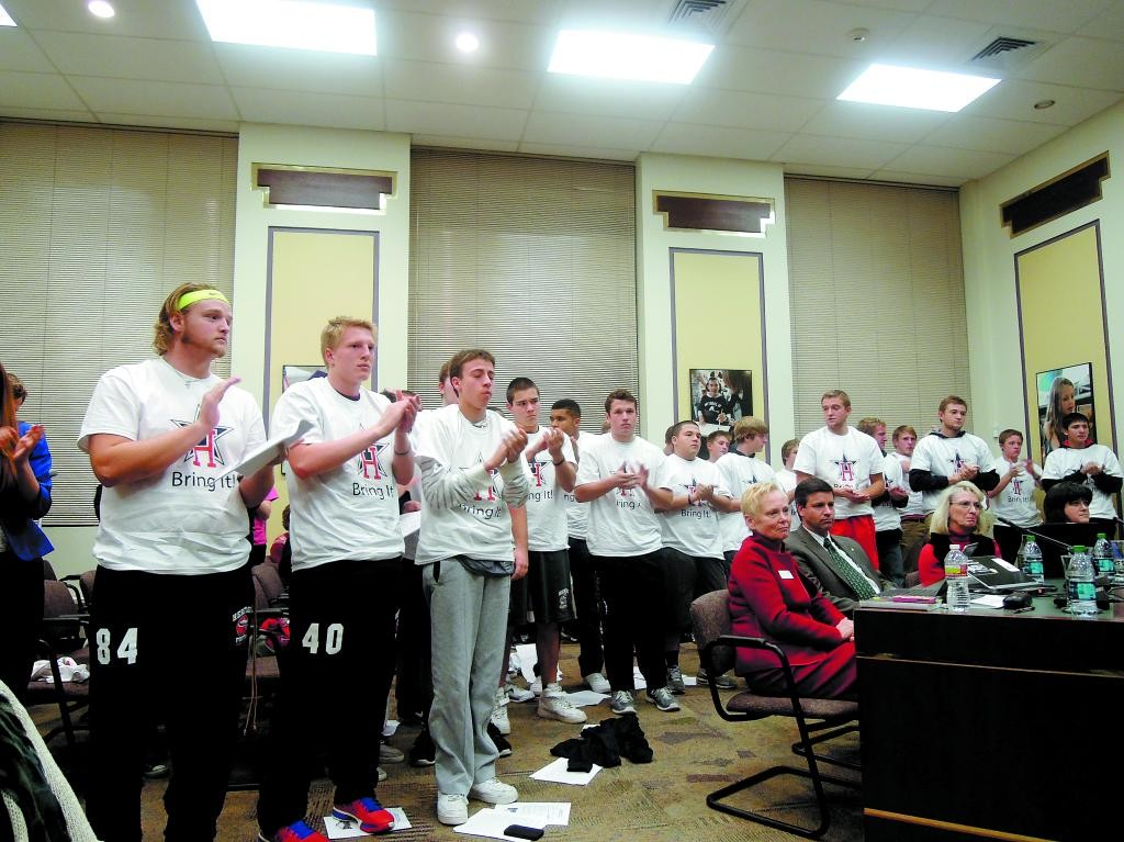The Heritage High School football team applauds Mike Griebel's plea for reinstatement during the Dec. 12 school board meeting. Photo by Jennifer Smith